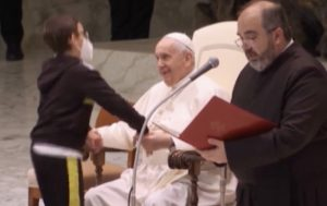 Sale sul palco e si siede accanto al Papa